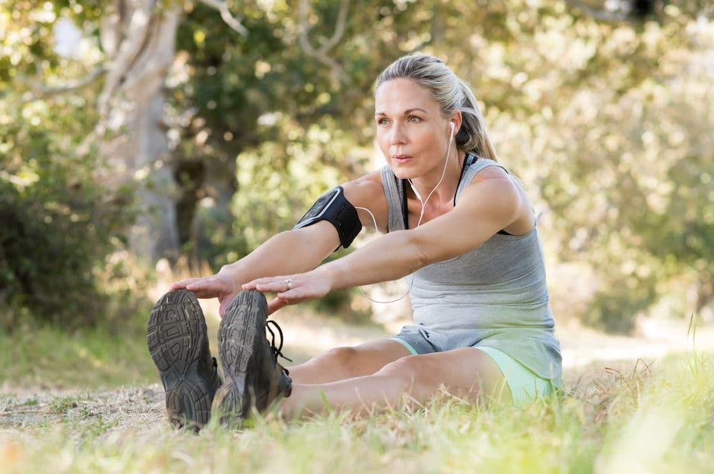 Senior woman exercising in park while listening to music. Senior woman doing her stretches outdoor.