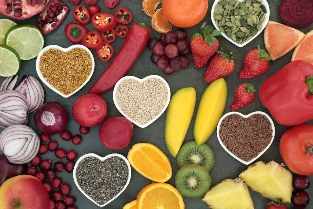 Paleo diet health and super food of fruit, vegetables, nuts and seeds in heart shaped bowls on slate