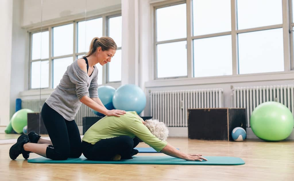 Physical Trainer Helping Elder Woman Doing Yoga
