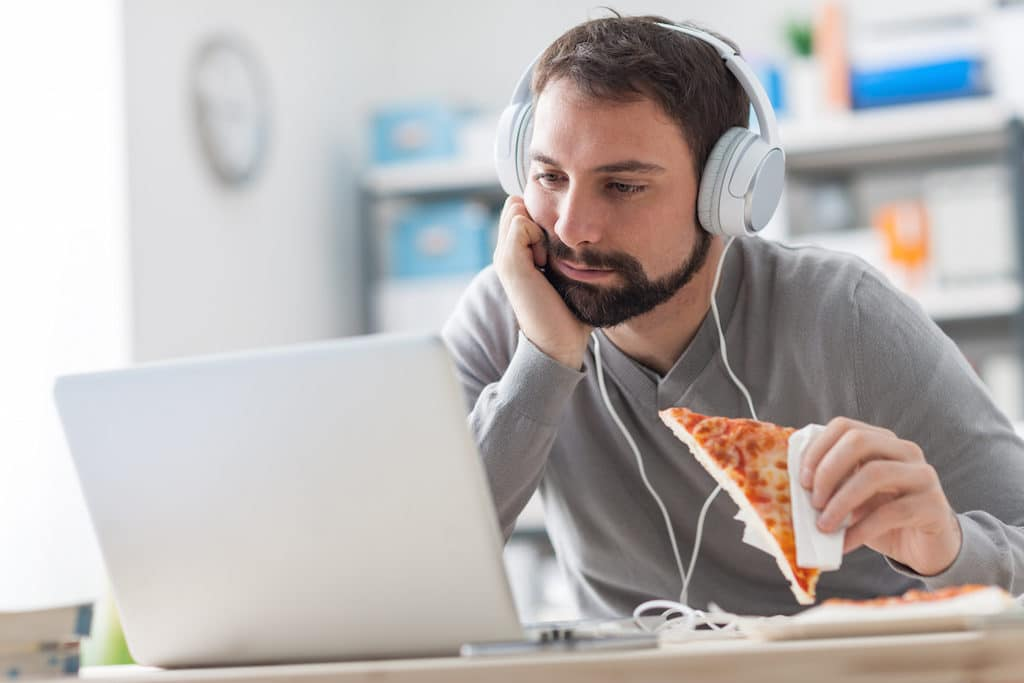 Lazy man sitting at desk using a laptop and having a ready meal he is holding a slice of pizza