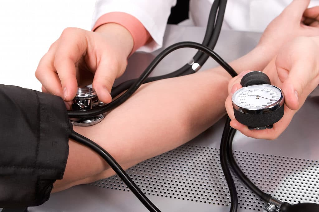 doctor checking blood pressure with stethoscope and sphygmomanometer