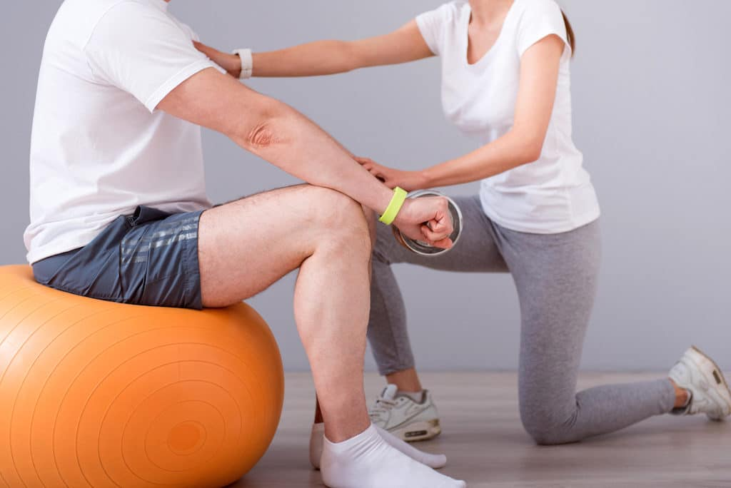 Rehabilitation together. Cropped image of male patient sitting on a gym ball with dumbbells during physical therapy praxis and female physiotherapist exercising with him