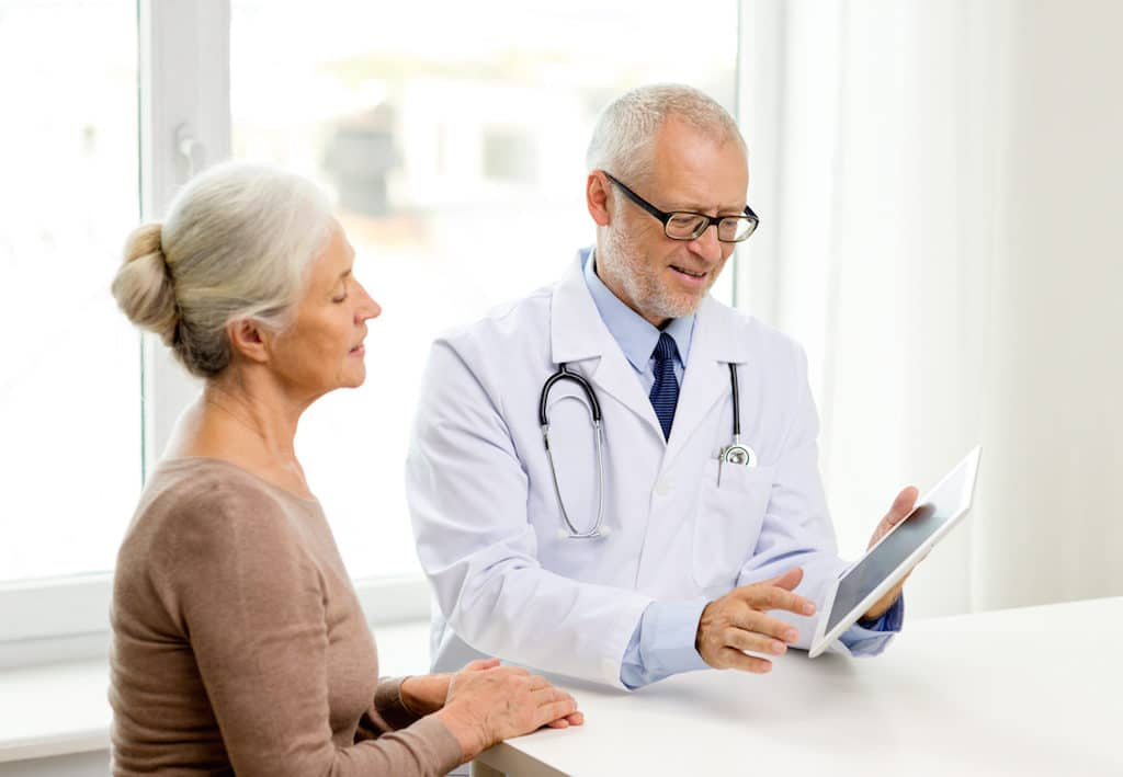 medicine, age, health care and people concept - smiling senior woman and doctor with tablet pc compu