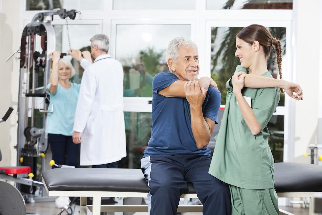 Nurse Guiding Senior Patient In Arm Exercise At Rehab Center