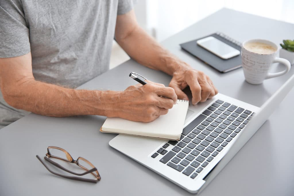 Man working with laptop and writing in notebook