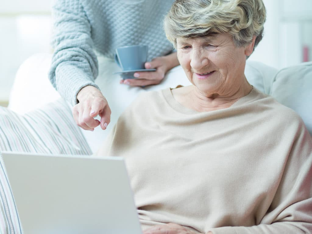Elder woman with laptop surfing on the internet
