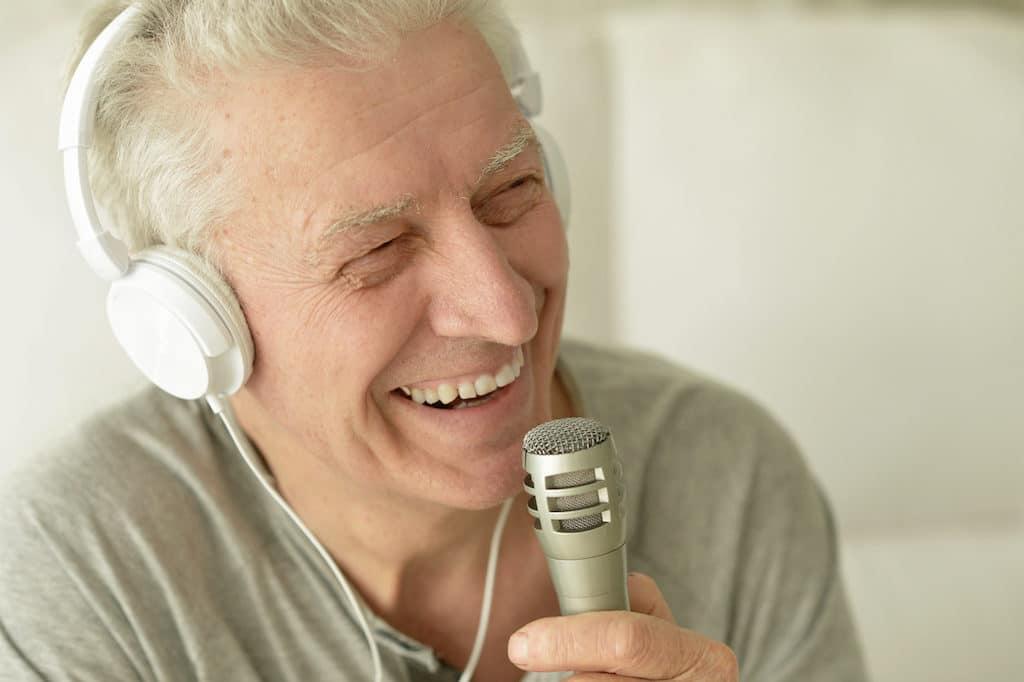Senior man singing into microphone in headphones